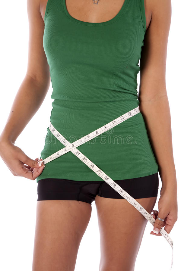Closeup measuring waist. A woman using a measuring tape to see the loss of weight to her waist stock photos