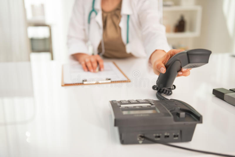 Closeup on medical doctor woman talking phone. In cabinet royalty free stock photo