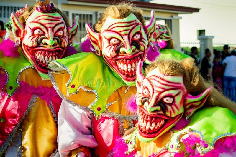 Closeup men in pied scary clowns costumes pose for photo at dominican carnival. Concepcion De La Vega, DOMINICAN REPUBLIC - FEBRUARY 09, 2020: closeup men in stock photo