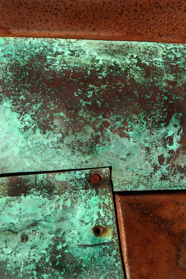 Rust and Patina. Closeup of metal with green copper patina and rusted sections forming an abstract composition royalty free stock photo