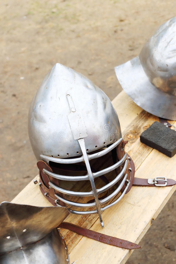 Closeup of metal medieval helmets with leather straps stock photos