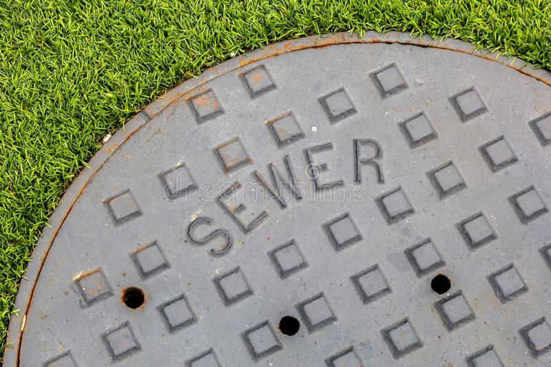 Sewer and grass. A closeup of a metal sewer cover next to fake grass landscape royalty free stock image