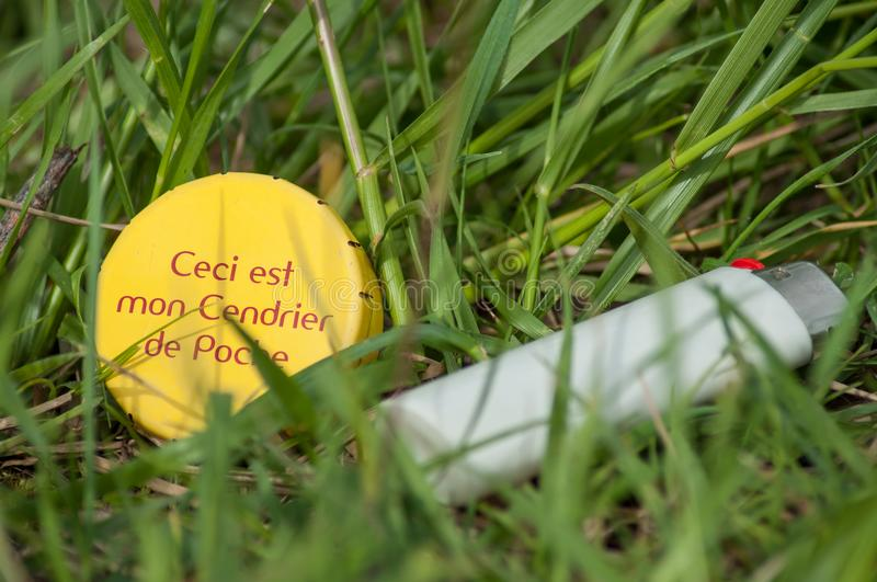 Metallic pocket ashtray with texte in french in the g. Closeup of metallic pocket ashtray with texte in french in the grass `this is my pocket ashtray` ceci est royalty free stock image