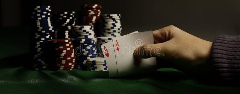 closeup Microplaquetas do casino e cartões de jogo na mão do ` s do jogador foto de stock