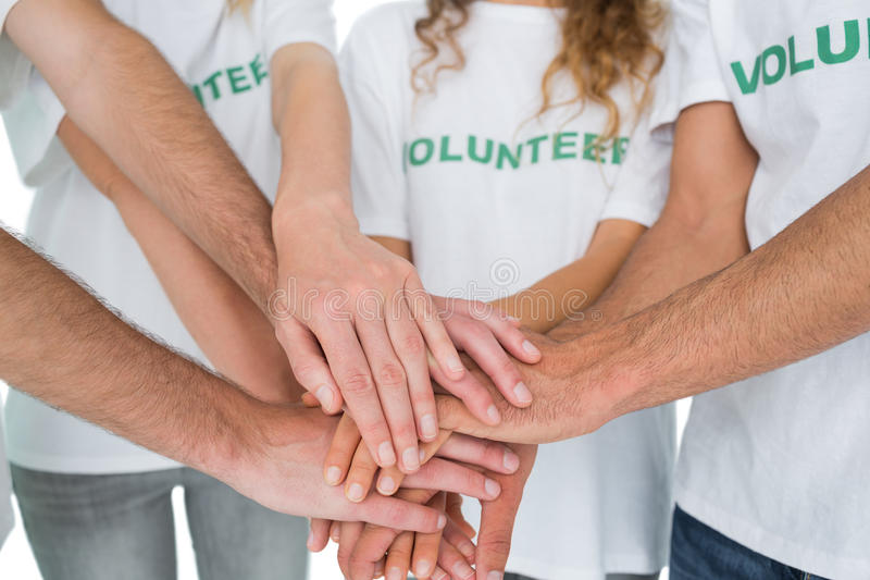 Closeup mid section of volunteers with hands together. Over white background royalty free stock photography