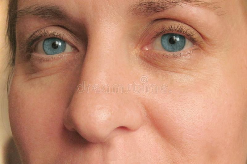 Closeup of middle aged woman face with blue eyes. Real skin without make up and correction. Look at camera.  Smiled stock photo