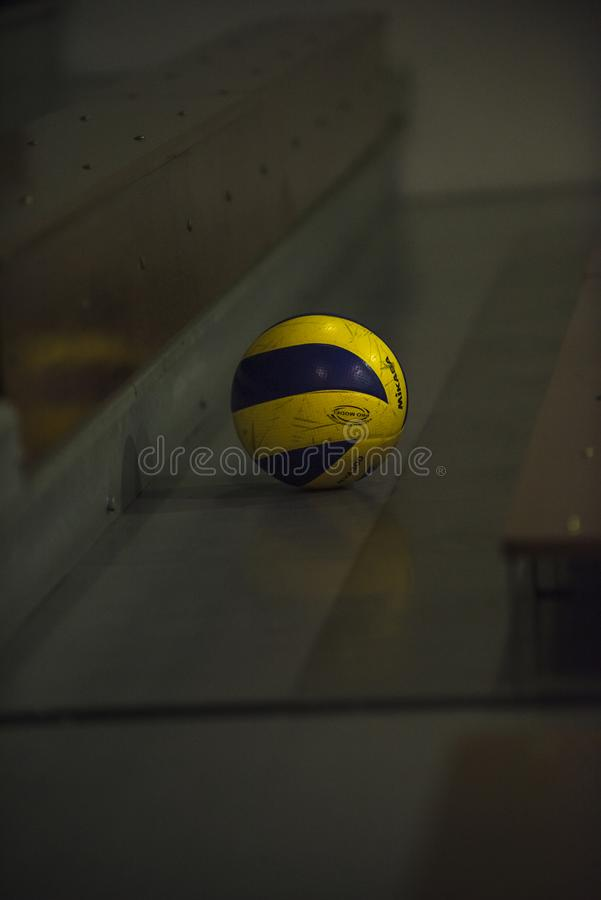 Closeup of a Mikasa Volleyball left on a seating sections in an indoor school gym. stock image