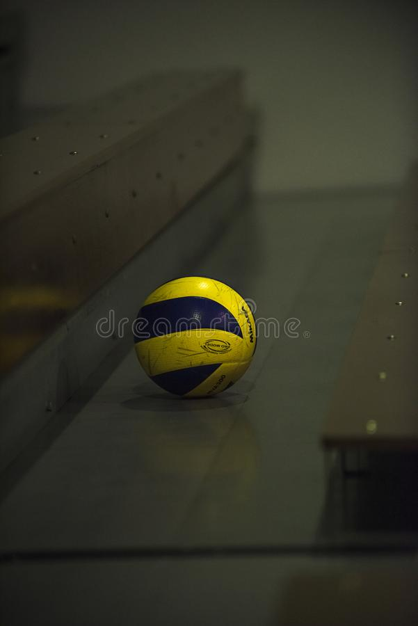 Closeup of a Mikasa Volleyball left on a seating sections in an indoor school gym. stock photos