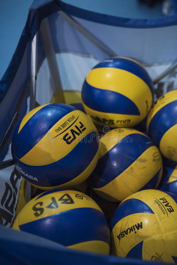 Closeup of Mikasa Volleyballs in a movable sport cart storage in an indoor school gym. royalty free stock image