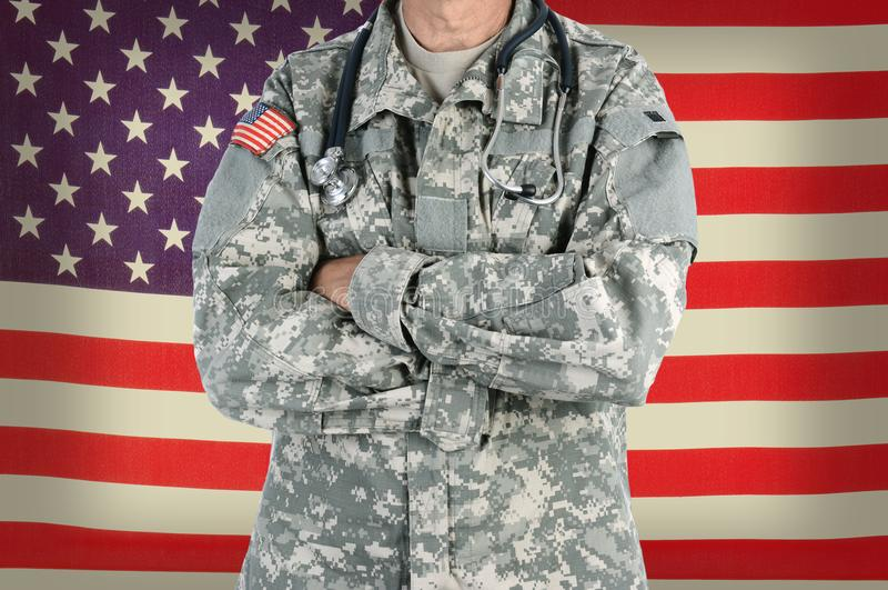 Military Doctor in Combat Uniform. Closeup of a military doctor with a stethoscope around his neck in front of American Flag. The man is wearing camouflage stock images