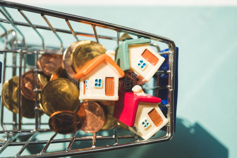 Closeup miniature house with golden stack coins in mini shopping. Cart using as business, property and financial concept - Vintage filter, aerial, background royalty free stock photos