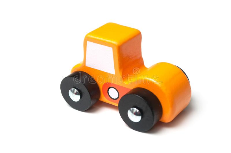 Miniature toy, wooden orange color car on white background. Closeup of miniature toy, wooden orange color car on white background stock image