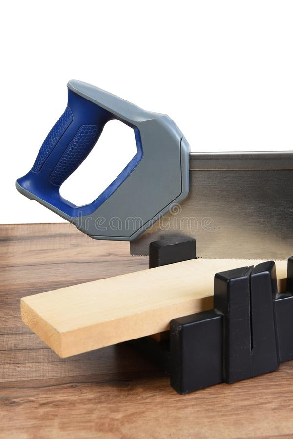 Closeup of a miter box and saw ready to cut a board at an angle stock image