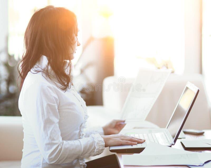 closeup modern affärskvinna som arbetar med dokument som sitter på hennes skrivbord arkivfoto