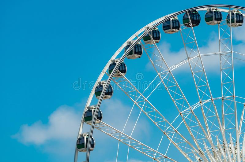 Closeup modern Ferris wheel against blue sky and white clouds. Ferris wheel at funfair for entertainment and recreation on holiday royalty free stock photo