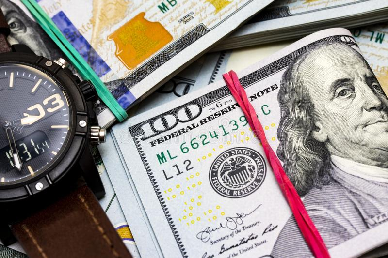 Closeup of modern hand watch lying on background made from one hundred dollar royalty free stock photos