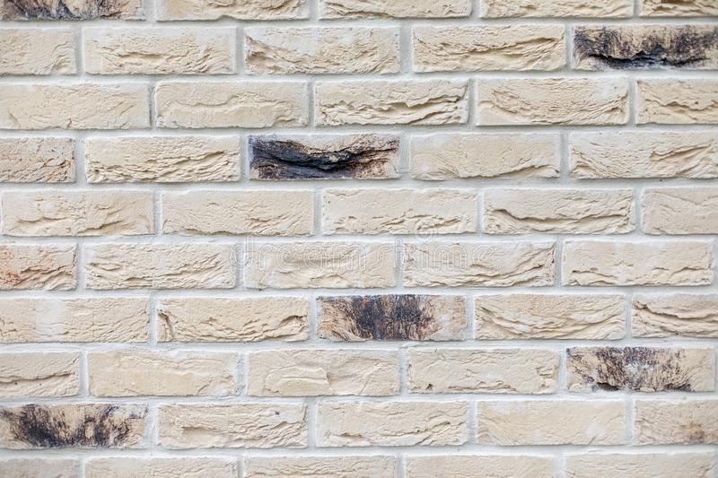 Closeup of modern neutral beige brick wall with dark bricks stock photos