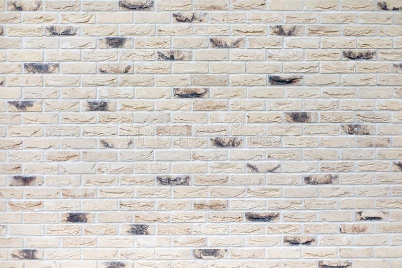 Closeup of modern neutral beige brick wall with dark bricks stock photo