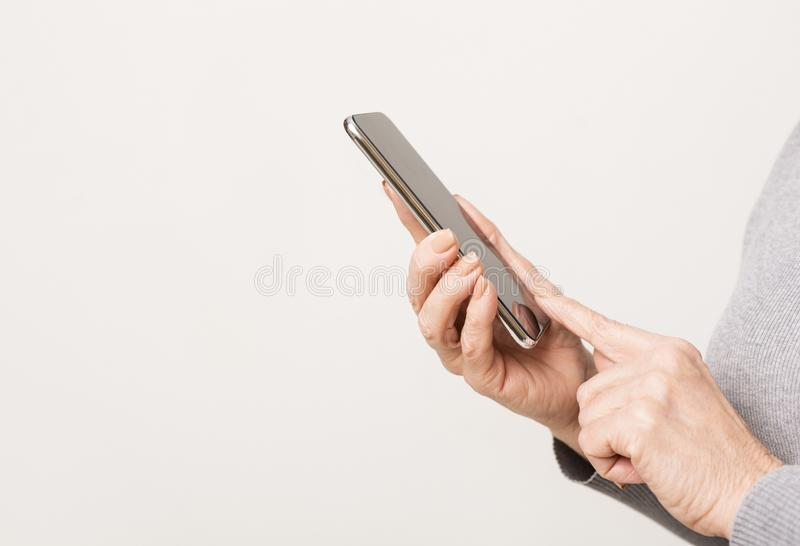Closeup of modern smartphone in mature woman`s hands stock image