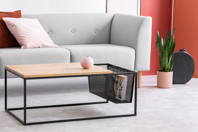 Closeup of modern wooden and metal coffee table next to stylish grey couch in trendy living room stock photo