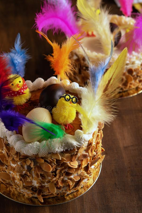 Closeup of a mona de pascua, a cake eaten in Spain on Easter Monday, ornamented with feathers and a teddy chick on on a rustic. Wooden surface. Vertical stock photos