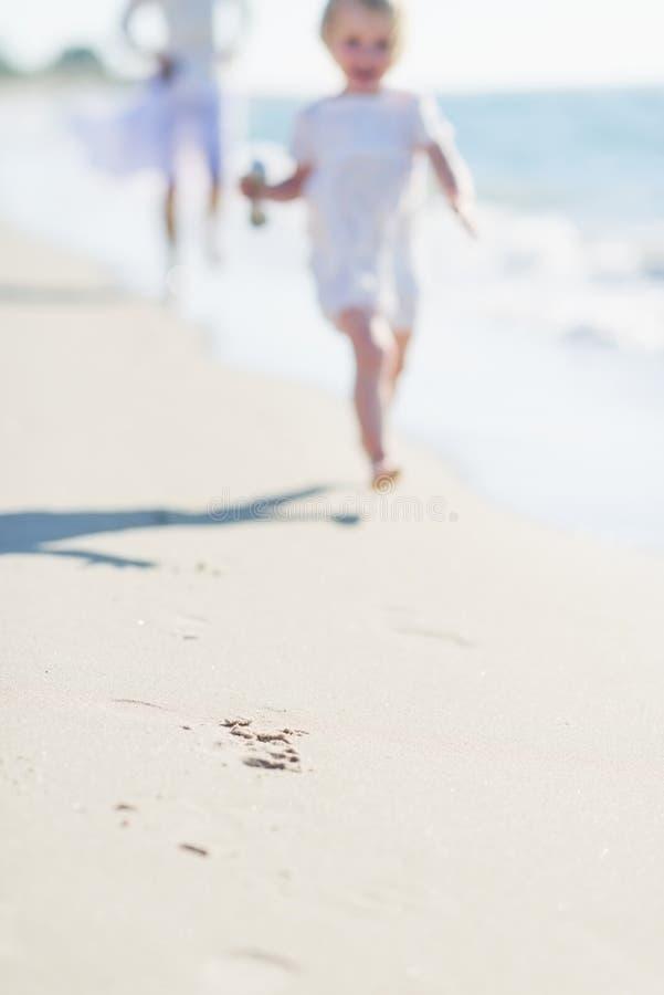 Closeup on mother and baby running along sea shore stock photos