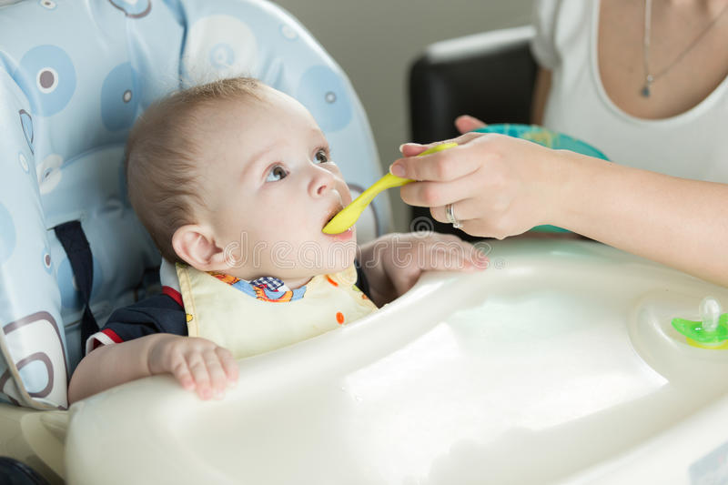 Closeup of mother giving porridge to her baby boy from plastic s royalty free stock images