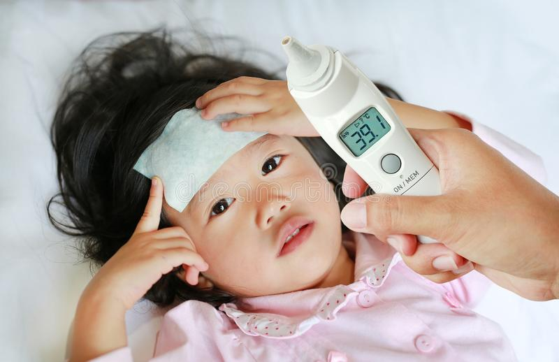 Closeup mother hand takes temperature for her daughter with ear thermometer on bed at home stock photo
