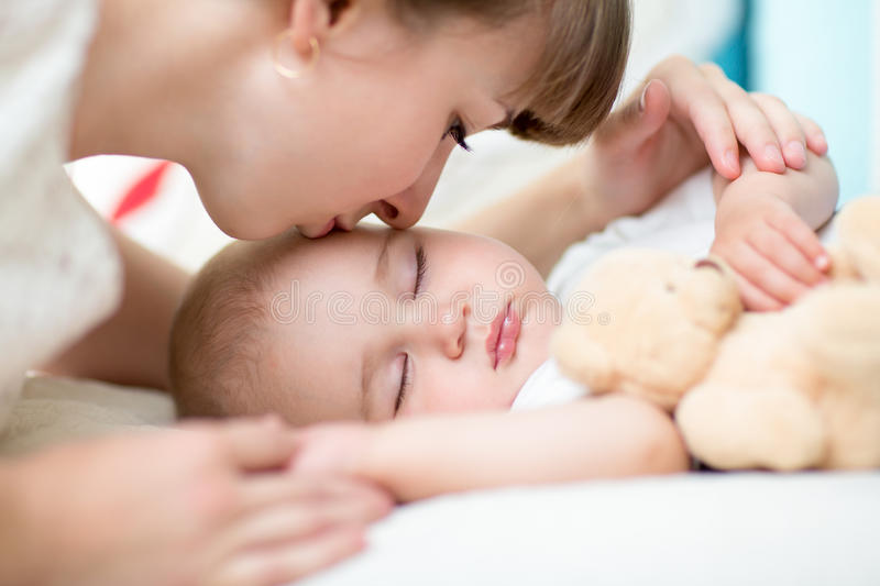 Closeup on mother kissing sleeping baby. Son royalty free stock image