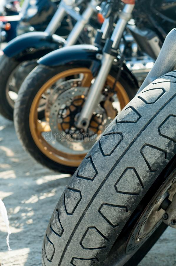 Closeup of a motorcycle tire with blurred background in sunny day. A closeup of a motorcycle tire with blurred background in sunny day royalty free stock photos