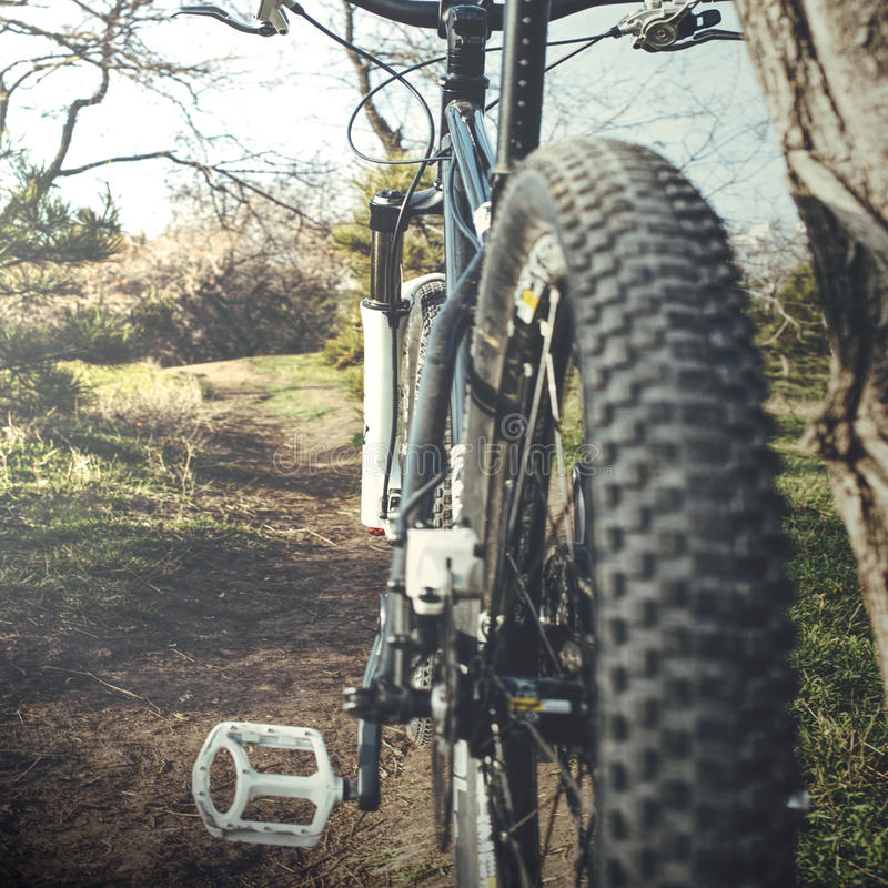 Closeup of mountain bike. With selective focus on frame and pedals and blurred tire pattern, countryside background stock image