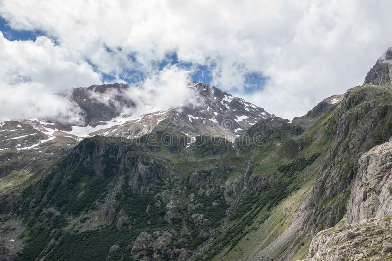 Closeup mountains scenes, walk to Trift Bridge in national park Switzerland. Europe. Summer landscape, sunshine weather, dramatic cloudy sky and sunny day royalty free stock photos