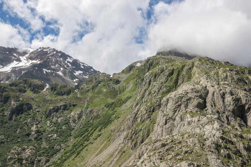 Closeup mountains scenes, walk to Trift Bridge in national park Switzerland. Europe. Summer landscape, sunshine weather, dramatic cloudy sky and sunny day stock photos