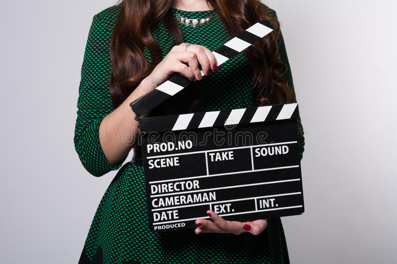 Closeup of a movie clapper keeps the girl in the green dress. Background for movie production royalty free stock photo