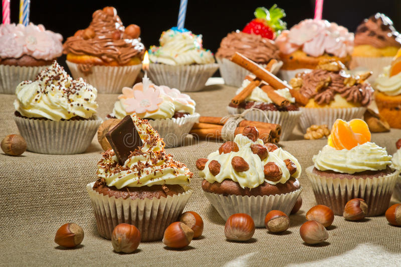 Closeup muffins with cream, chocolate and nuts stock images