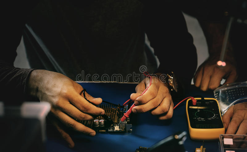 Closeup of multimeter measuring computer circuit board stock image
