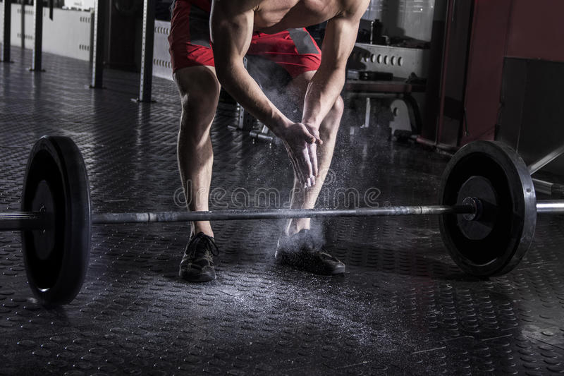 Closeup of muscular athlete clapping hands before barbell worko stock photography