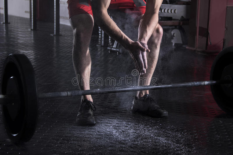 Closeup of muscular athlete clapping hands before barbell worko stock image