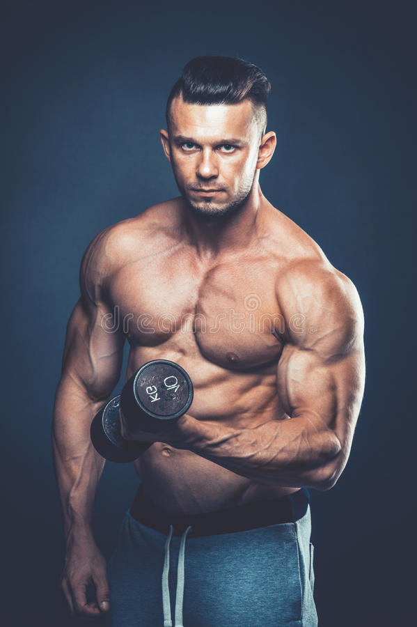 Closeup of a muscular young man lifting dumbbells weights on dar stock photos