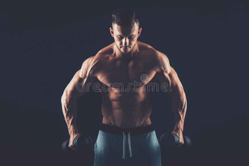 Closeup of a muscular young man lifting dumbbells weights on dar stock photography