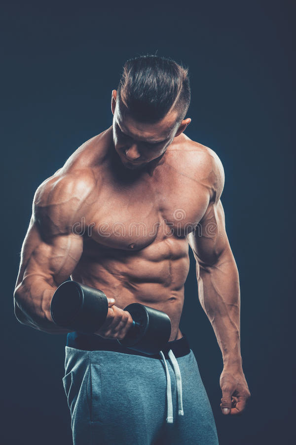 Closeup of a muscular young man lifting dumbbells weights on dar stock image