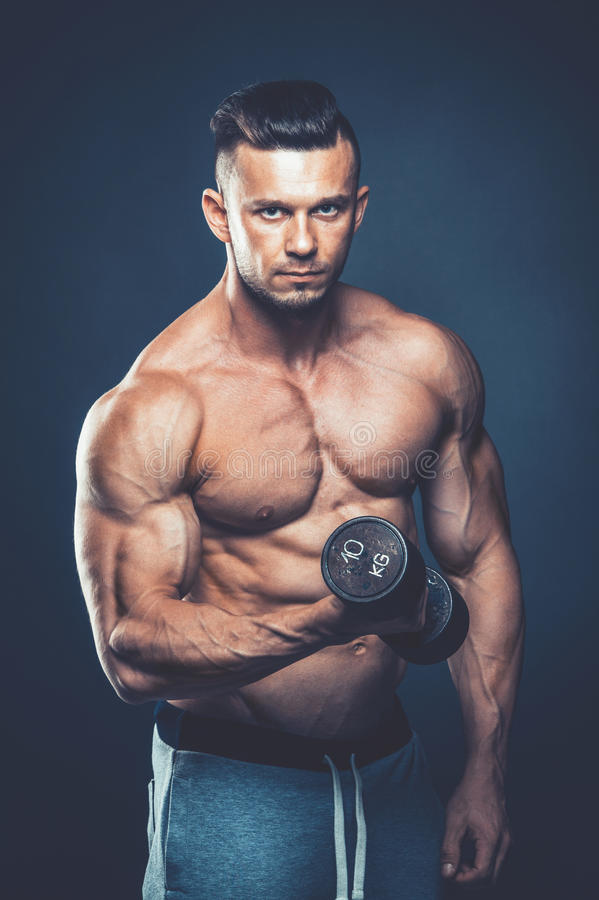 Closeup of a muscular young man lifting dumbbells weights on dar stock photo