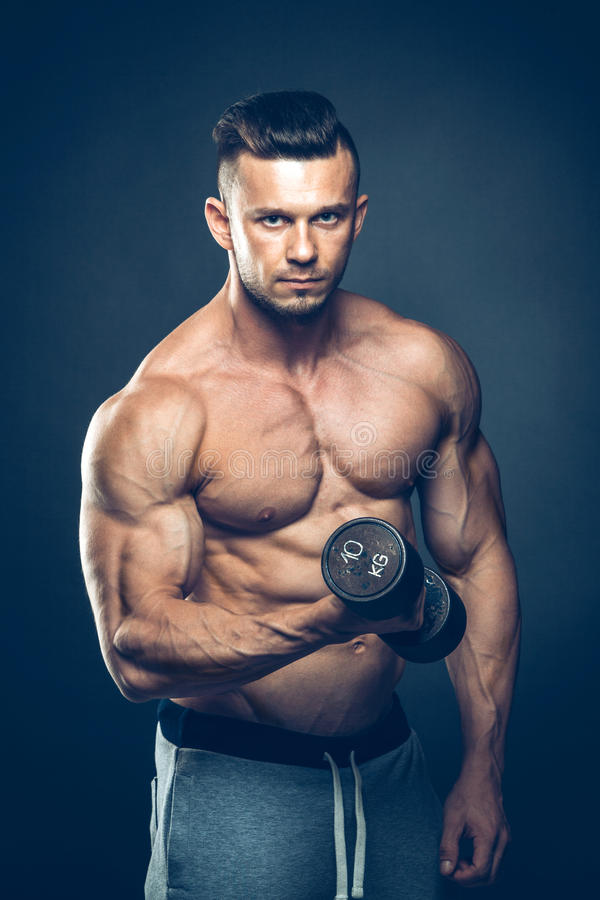 Closeup of a muscular young man lifting dumbbells royalty free stock photography