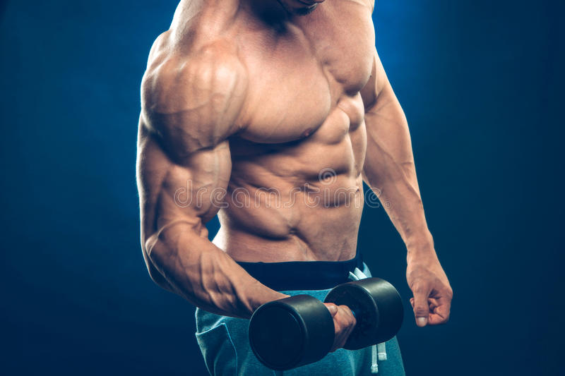 Closeup of a muscular young man lifting dumbbells stock photography