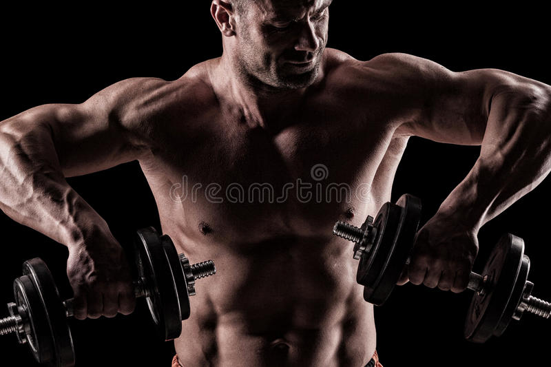 Closeup of a muscular young man lifting weights on dark background royalty free stock photo
