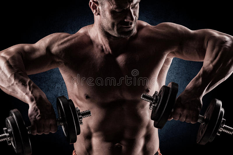 Closeup of a muscular young man lifting weights on dark background royalty free stock images