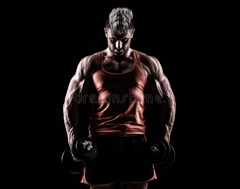 Closeup of a muscular young man lifting weights on dark background stock images