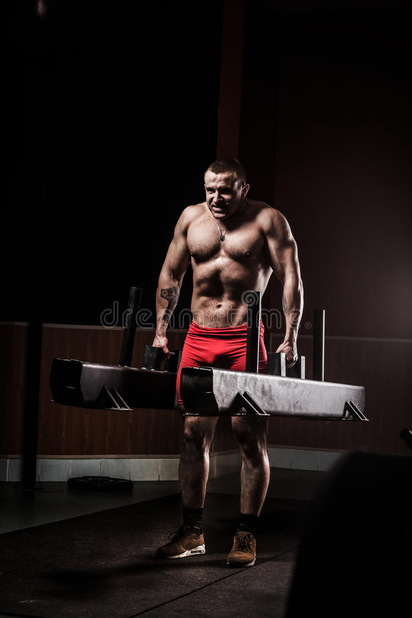 Closeup of a muscular young man lifting weights. royalty free stock photography