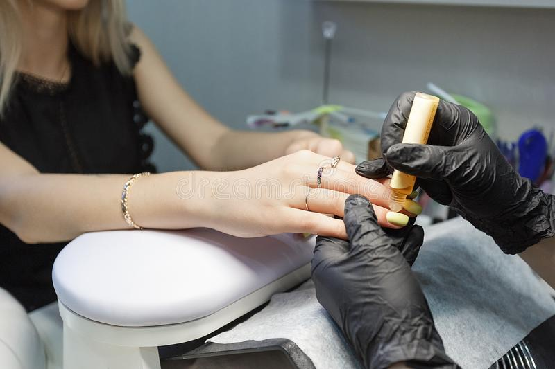 Closeup on nail master wearing black gloves making acrylic nails in salon. Concept of visiting beauty shop. Closeup on nail master wearing black gloves making royalty free stock photos