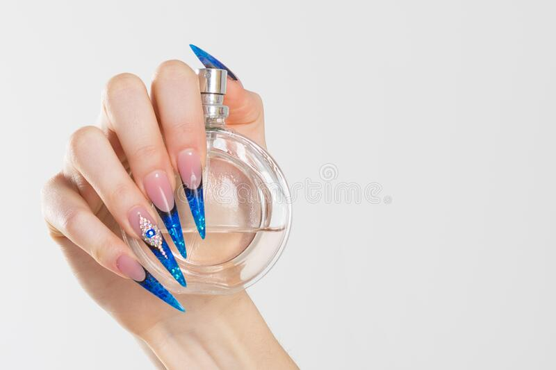 Closeup nail polished blue stiletto nails with crystals, hand holding perfume bottle isolated on white grey background wall with. Copy space. Winter nails royalty free stock photos